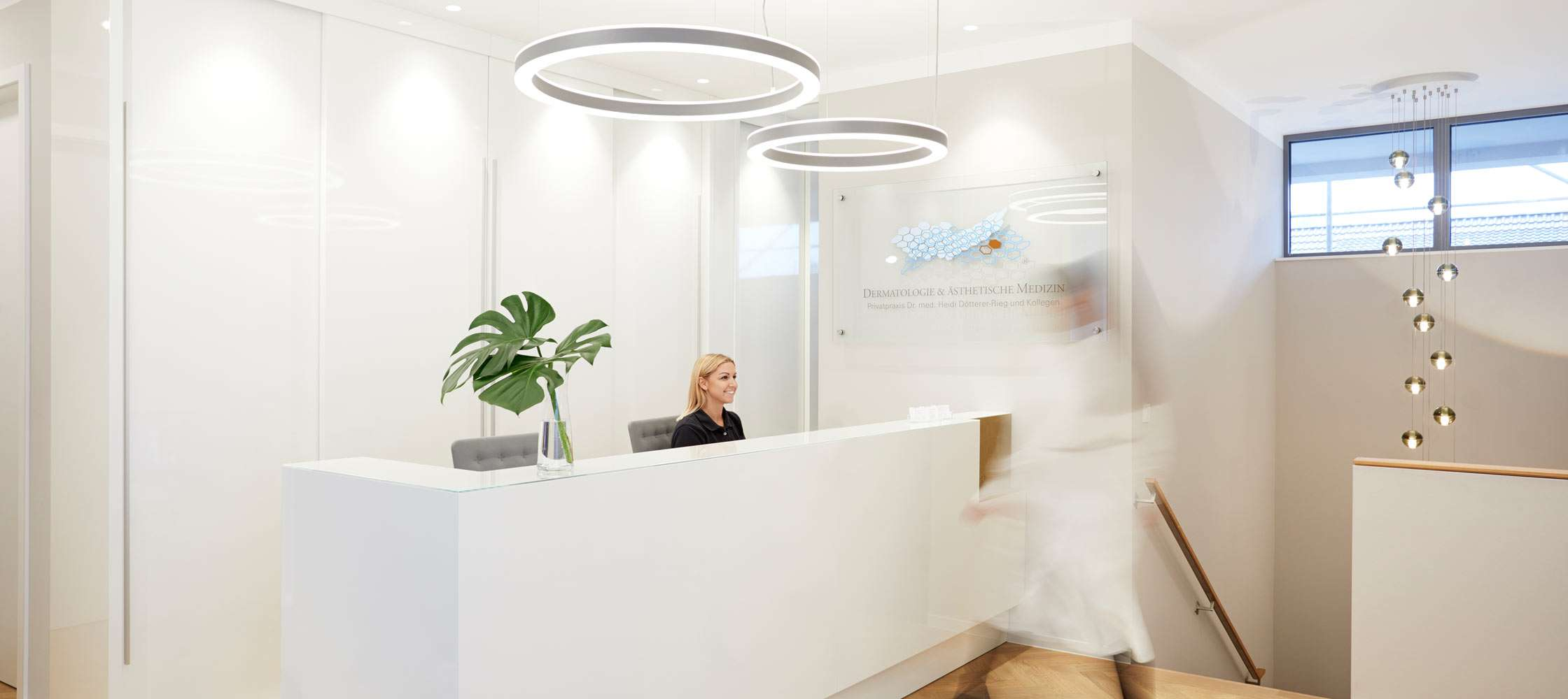 Reception of the dermatology private practice in Frankfurt near Fressgass. A staircase leads to the hallway where stands a bar for the reception of patients. The practice logo on glass is affixed on a wall. Futuristic ceiling lights brighten the room.