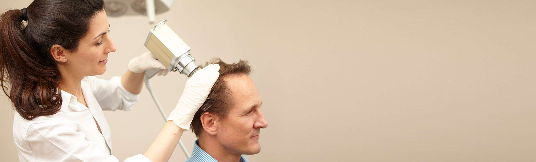 A doctor treats a patient after a detailed consultation with the mesotherapy gun against hair loss. The hair roots at the head of a male person are stimulated by the injections with the mesotherapy gun.