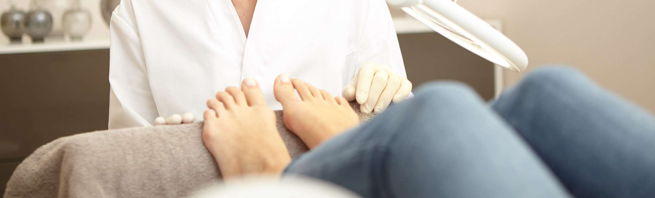 Feet a patient at a nail treatment. Clean and healthy nails can be seen after a podiatric treatment. The patient's legs are dressed in blue jeans. The treating podiatrist has sterile gloves.